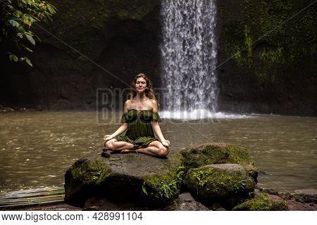 Yoga Lotus Pose. Young Caucasian Woman Sitting On The Stone, Meditating, Practicing Yoga, Pranayama