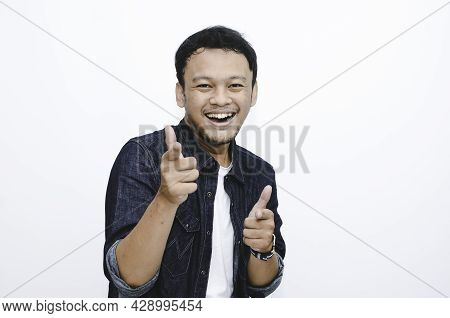 Asian Young Man Pointing Forward, Looking At Camera, Make Choosing You Gesture Against White Backgro