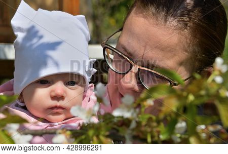Portrait Of A Mother And Newborn With A Blossoming Cherry With Flowers