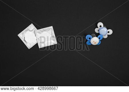 Condoms Or Baby Pacifiers, Methods Of Contraception On Black Background. Prevention Of Unwanted Preg