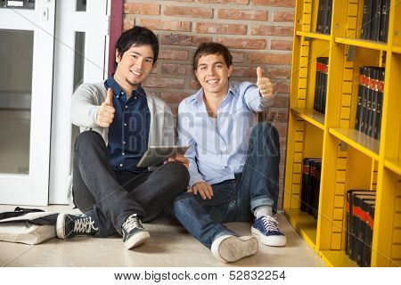 Full length portrait of multiethnic friends with digital tablet gesturing thumbsup while sitting in college library