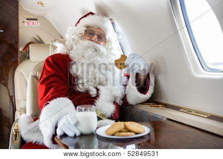 Portrait of man in Santa costume having cookies and milk in private jet