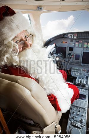 Portrait of man in Santa costume sitting in cockpit of private jet