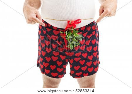 Horny guy with Christmas mistletoe around his waist, pointing at his crotch and asking for oral sex.  White background.