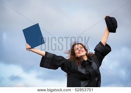 Pretty, young woman celebrating joyfully her graduation - spreading wide her arms, holding her diploma, savouring her success  poster