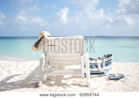 Sun Lounge On A Beach With Hat And Bag