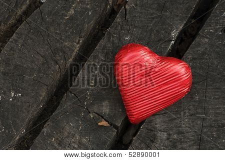 Red wrapped heart on wooden background. Valentines heard shape poster