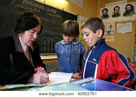 Children Pupils, Boy And Girl Look Like A School Teacher Checks Homework.