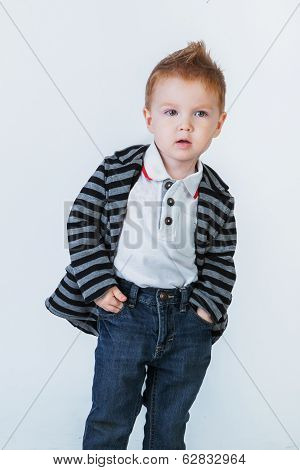 Little Cute Boy In A Striped Jacket Standing And Looking At The Camera