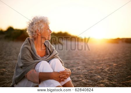 Old Woman Sitting On The Beach Looking Away At Copyspace