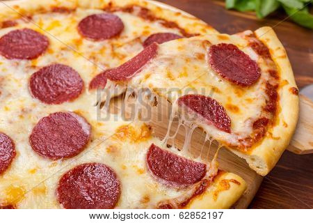 Slice of Pepperoni Pizza  being removed from whole pizza