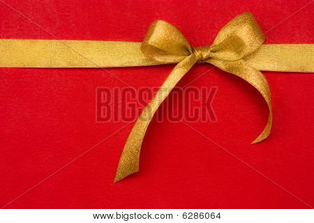 Golden Gift Ribbon And Bow On Red Background. Some Other You May Also Like
