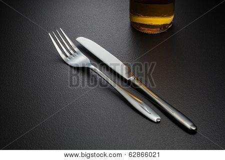 bottle of beer, knife and fork on black poster