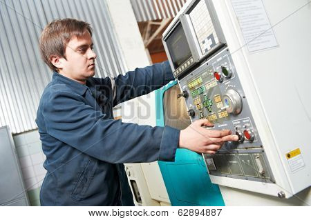 operative worker near cnc milling machine center at factory tool workshop