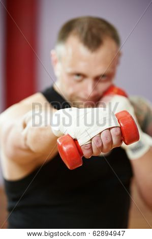 boxer man during boxing training doing excercise with dumbbells at fitness gym