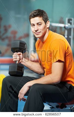 Smiling athlete man at biceps brachii muscles exercises with training dumbbells in fitness gym