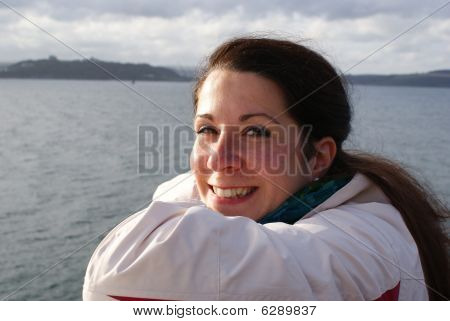 young woman smiling in front of the coastline