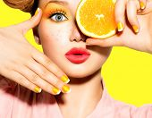 Beauty Model Girl takes Juicy Oranges. Beautiful Joyful teen girl with freckles, funny red hairstyle, yellow makeup and nails. Professional make up. Orange Slices.   poster