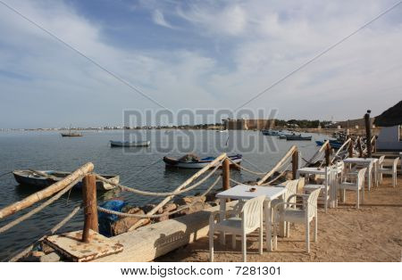 view over the old fishing harbor of Houmt Souk/Djerba/Tunisia with the fort Bordj el kebir in the background poster