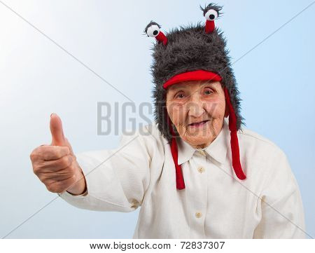 Grandma In Funny Hat Shows Thumbs Up