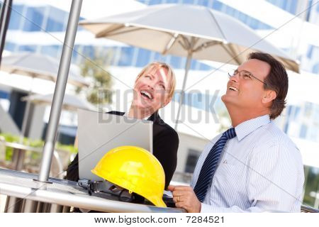Businesswoman And Man Laughing While Working