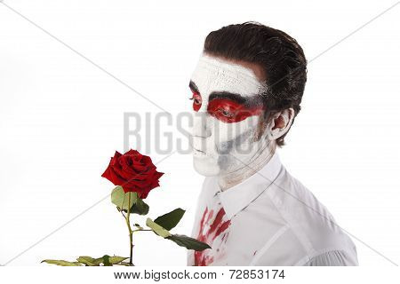Man With White Mascara And Bloody Shirt Holds Red Rose
