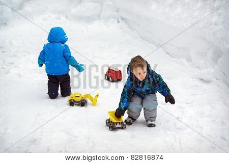Two Boys Playing In Snow With Trucks