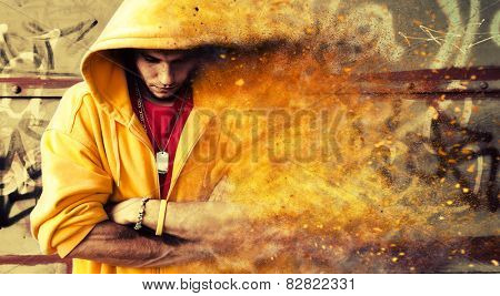 Young man portrait in hooded sweatshirt, jumper on grunge graffiti wall. Particles effect