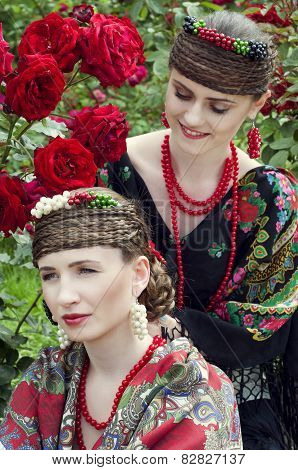 Two Caucasian Slavonic Women Sitting In The Field Of Flowers