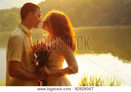 Couple Of Young Lovers Hugging In The Sunset Light