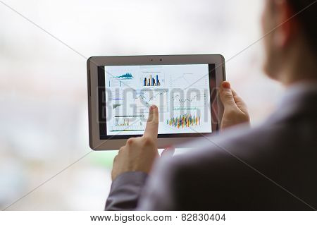 Business person analyzing financial statistics displayed