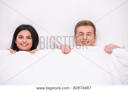 Happy couple is under blanket looking at camera