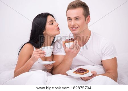 Young couple sitting under white blanket early in the morning and having their breakfast in bed. Woman with cup of coffee kissing her husband while he eating toasts with jam poster