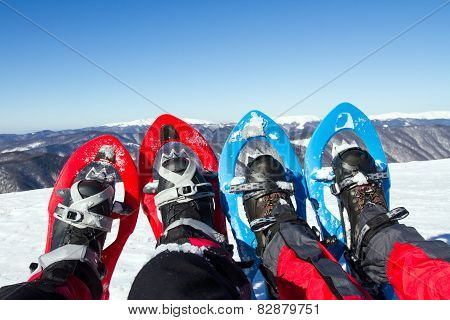 Snowshoeing - woman trekking in winter mountains.