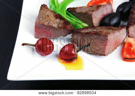meat food : roasted fillet mignon on white plate with tomatoes apples and chili pepper over black wooden table