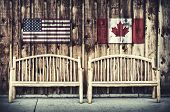 Two rustic wooden log benches sit side by side outdoor against a building wall made of wooden siding with a USA and Canada flag hanging on the wall just above the benches. A grunge layer is added to a USA and Canada flag. Filtered for a retro vintage look poster