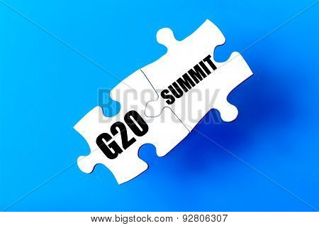 Connected puzzle pieces with words G20 and SUMMIT against blue background. Concept image with copy space available. poster