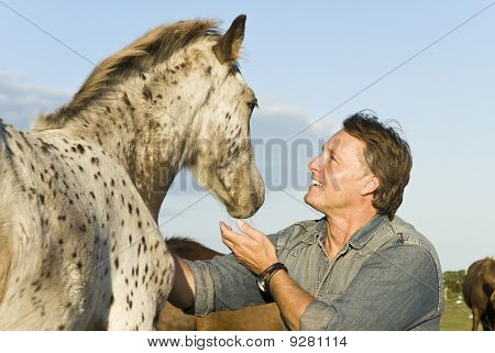 happy man petting his horse