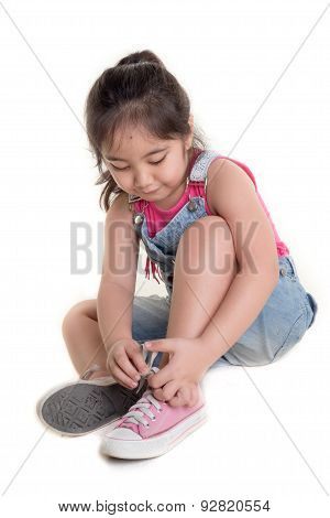 Little Asian Child practices to tying her shoes on isolated background