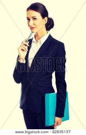Beautiful pensive businesswoman holding a pen.
