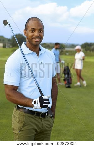 Closeup portrait of athletic young male golfer with golf club, smiling, looking at camera.