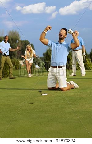 Young male golfer kneeling happy at hole after successful putt, shouting happy with hands fisted.