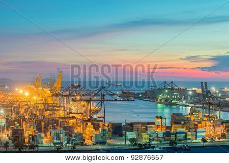 Container Cargo Freight Ship With Working Crane Bridge In Shipyard At Dusk For Logistic Import Expor