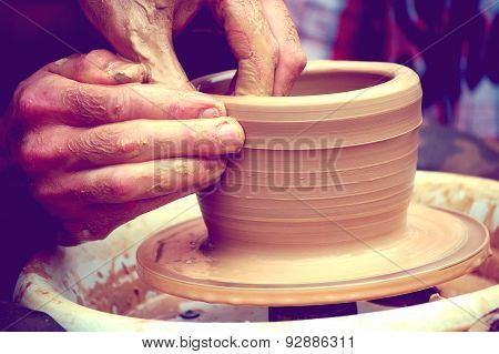 The potter molds a jug on the circle