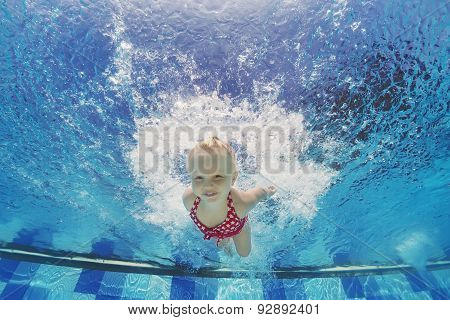 Child Swimming Underwater With Splashes In The Pool