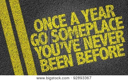 Once a Year Go Someplace You've Never Been Before written on the road