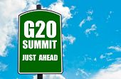 G20 SUMMIT Just Ahead written on green road sign against clear blue sky background. Concept image with available copy space poster