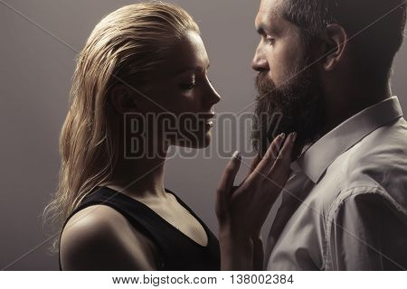young sexy couple of pretty woman with blonde hair and handsome bearded man with long beard embracing on grey background