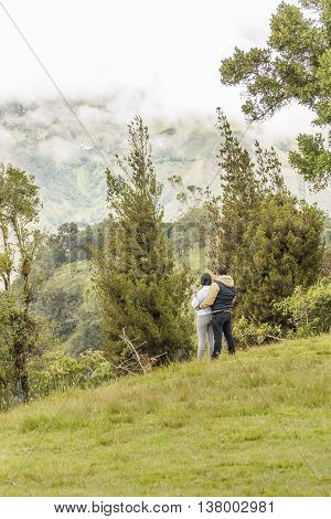 BANOS, ECUADOR, OCTOBER - 2015 - Adult couple hugging at the top of hill in Banos Ecuador