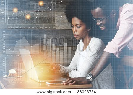 Happy African Freelancer Watching His Female Partner With Afro Haircut Showing Graphics, Demonstrati